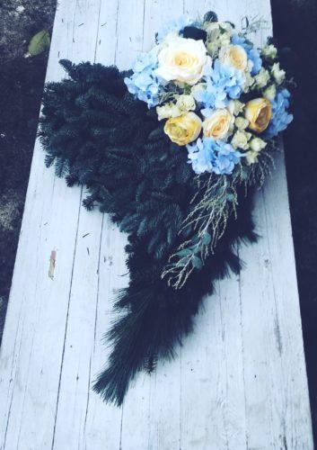 dekoracja na grób w kształcie serca z niebieskimi i żółtymi kwiatami