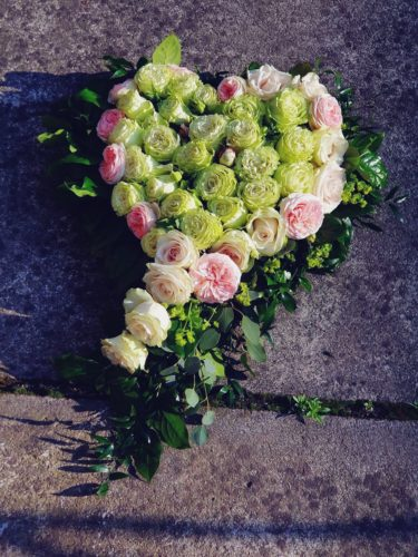 dekoracja na grób w kształcie serca z zielonymi i różowymi kwiatami