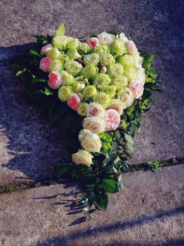 dekoracja na grób z zielonhmi i różowymi kwiatami